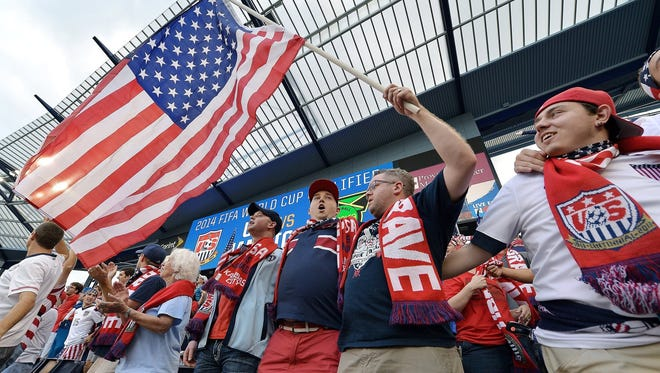 Clint Krahn, holding the American flag, and other Sioux Falls American Outlaws fans, attend a game against Jamaica in Kansas City in 2013.