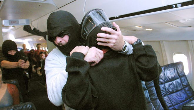 A federal air marshal (far L) fires on a hijacker (C) who is holding a knife to the throat of a flight crew member (R) during a simulation of a hijacking at a tactical training  program.