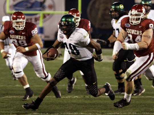 - -Oregon quarterback Dennis Dixon scrambles away from the rush of Oklahoma's Dusty Dvoracek, right, and C.J. Ah You, left, in the first quarter of the Holiday Bowl Thursday Dec. 29, 2005 in San Diego. Dizxon turned the scramble into a two yard gain. (AP Photo/Lenny Ignelzi)