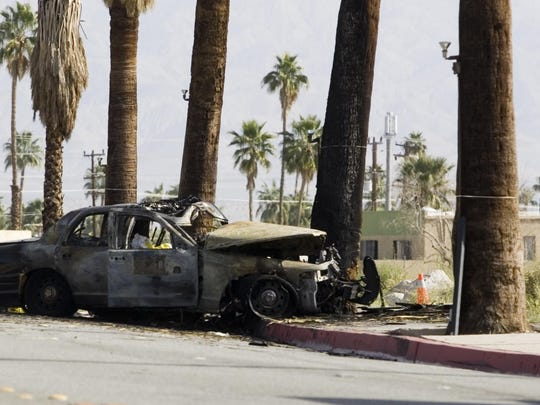 The burned vehicle of Officer Jermaine Gibson sits on Palm Canyon Drive after he was killed on March 18, 2011.