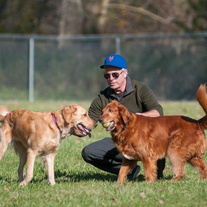 Matt Adair, of Port Huron, plays with his two golden