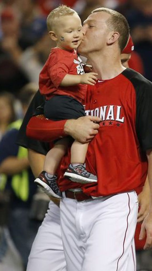 Reds third baseman Todd Frazier kisses his son, Blake,