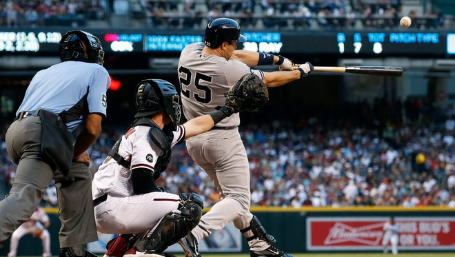 New York Yankees' Mark Teixeira (25) connects for a single as Arizona Diamondbacks catcher Chris Herrmann and umpire CB Bucknor, left, watch during the first inning of a baseball game, Monday, May 16, 2016, in Phoenix.