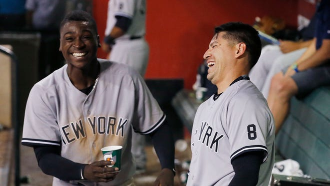 New York Yankees' Jacoby Ellsbury, right, laughs as Didi Gregorius, left, delivers some water for Ellsbury after Ellsbury scored a run after hitting a triple and scoring on a throwing error on the play during the fifth inning of a baseball game, Monday, May 16, 2016, in Phoenix.
