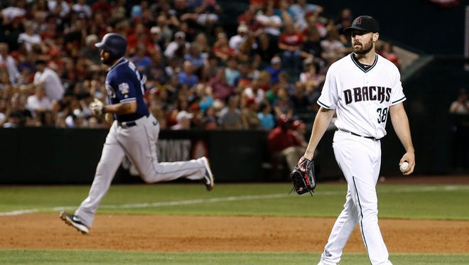 Arizona Diamondbacks' Robbie Ray (38) walks back to the mound with a new baseball after giving up a home run to San Diego Padres' Matt Kemp, left, during the fifth inning of a baseball game Friday, May 27, 2016, in Phoenix.