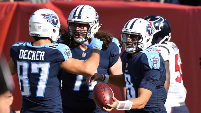 Tennessee Titans quarterback Marcus Mariota (8) celebrates with guard Dennis Kelly (71) and wide receiver Eric Decker (87) after a touchdown run during the first half against the Houston Texans at Nissan Stadium.