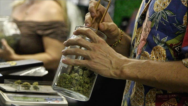 A budtender weighs cannabis for a patient at P.S.A. Organica in Palm Springs.