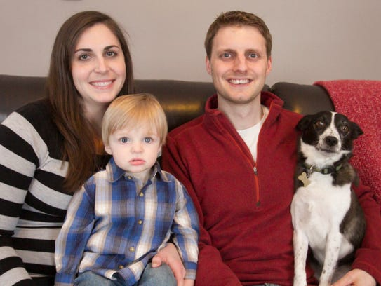 Nicole and Nicholas Alimpich pose with their 17-month-old son, Robert, and dog, Bailey, on Thursday, Mar. 8, 2018 in their Brighton Township home.