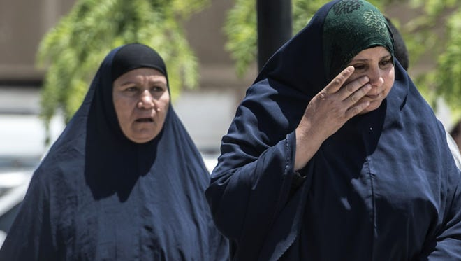 A relative of a passenger who was flying aboard an EgyptAir plane that vanished from radar en route from Paris to Cairo overnight cries as family members are transported by bus to a gathering point at Cairo airport on May 19, 2016.