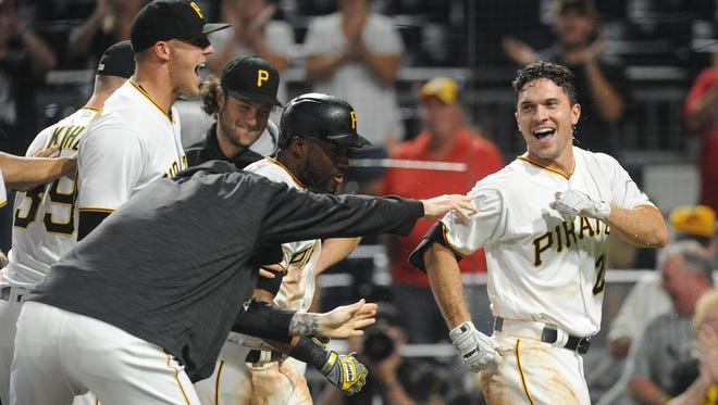 Adam Frazier (right) of the Pirates celebrates with his teammates after hitting a two-run walk-off homer off Brewers closer Corey Knebel in the bottom of the ninth inning Wednesday night in Pittsburgh.