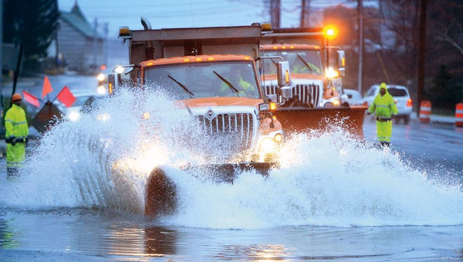 Road crews work on clearing a flooded road in Norwalk Conn., using snowplows to clear the more than foot deep water, Tuesday, Dec. 9, 2014.