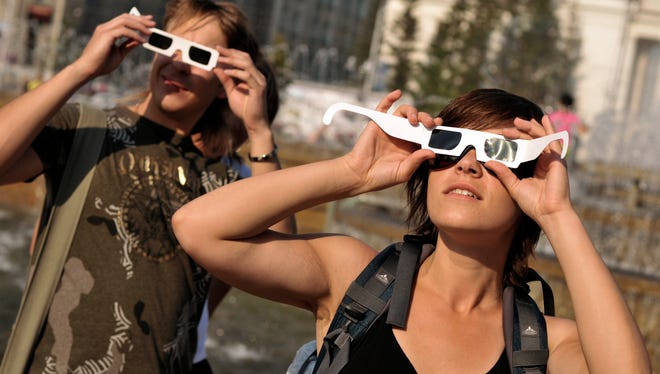 People check their eclipse glasses ahead of a solar eclipse in the Siberian city of Novosibirsk on Thursday, July 31, 2008. The Great American Eclipse of Aug. 2017 is leading to a tourist boon from Oregon to South Carolina.