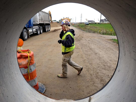 Laborer Linda Caplinger, of Fort Gratiot, walks in front of a piece of pipeline before it is laid into the ground Monday, Oct. 5, along Fisher Road in Grant Township.