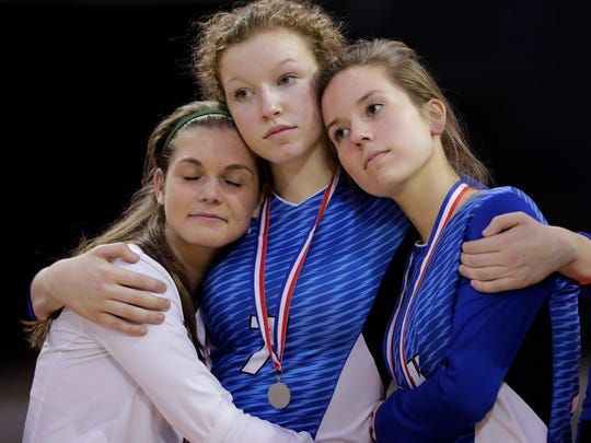 From left: Notre Dame's Whitney DeMeuse (1), Maddie Reitz (7), and Meghan Yakel (13) embrace after the Tritons lost to Waukesha Catholic Memorial in the Division 2 championship match at the WIAA state girls volleyball tournament at the Resch Center on Nov. 5.