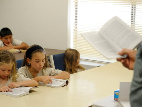 Bill Bruno, pictured near right, reads to Milea Rogers, 7, left, Riley Harris, 7, and Caroline Holland, 5. The children are challenging their reading skills by following along and learning about heroes of history, Alan Shepard, during a week-long reading camp at Prosperity Avenue Baptist Church, Tulare.