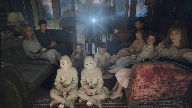 """Seated on the floor: the twins (Thomas and Joseph Odwell), Fiona (Georgia Pemberton) and Hugh (Milo Parker), Left to right: Emma (Ella Purnell), Jake (Asa Butterfield), Horace (Hayden Keeler-Stone), Miss Peregrine (Eva Green), Enoch (Finlay Macmillan), Claire (Raffiella Chapman), Bronwyn (Pixie Davies) and Olive (Lauren McCrostie) - are the very special residents of """"Miss Peregrine's Home for Peculiar Children."""""""