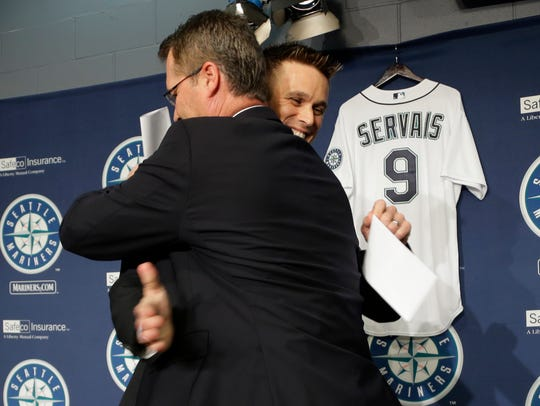 Scott Servais and Jerry Dipoto embrace after Servais