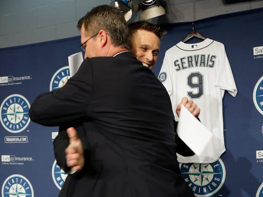 Scott Servais and Jerry Dipoto embrace after Servais was introduced as the new manager of the Seattle Mariners in October 2015.