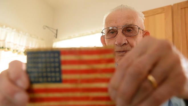 Bud Olson, a World War II veteran, holds up a 48-star American flag patch that he wore on his service uniform during World War II, when he served from Normandy to Berlin. Among the most challenging moments: liberating a concentration camp and losing green troops during heavy combat.