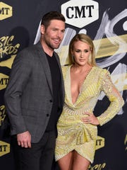 Carrie Underwood and husband Mike Fisher walk the red