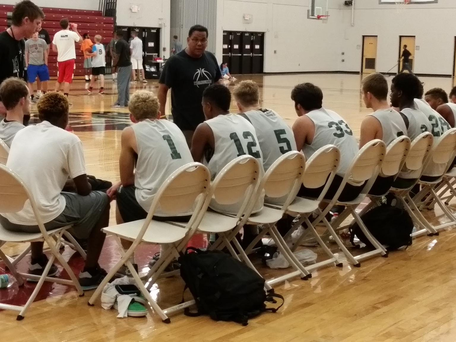 Melbourne boys basketball coach Michael Soliven talks to his team after winning the FIT boys basketball team camp title.