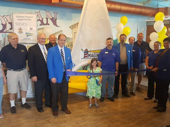"""Nine-year-old Willow Scott unveils her winning name """"Imagination"""" for the new SEAS exhibit at Above and Beyond Children's Museum to inspire Sheboygan kids about sailing. Willow then cut the ribbon on the new exhibit with Leslie Kohler, chairman of SEAS, Mayor Mike Vandersteen, Jeff Mehn, executive director of the museum, and Chamber ambassadors."""