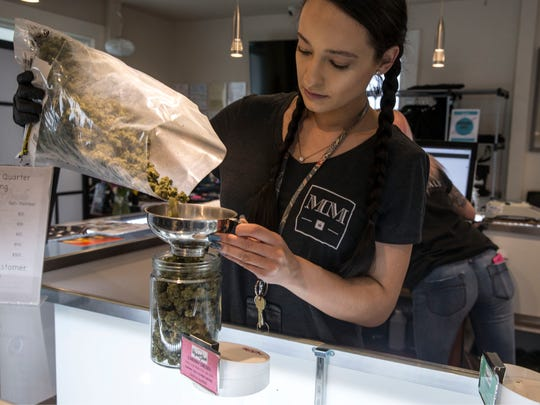 Raven Guillmette, store manager, measures out a strain of marijuana called Cherry Diesel. Higher Grade dispensary offers fine cannabis for medicinal purposes.  Denver, CO Thursday, April 12, 2018 @dhoodhood