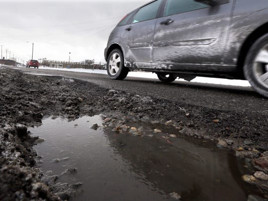 In a photo taken Feb. 18 in Highland Park, a large pothole is seen on Oakland Ave. A University of Michigan survey released today shows most local government leaders want more state money for roads but few support raising the sales tax to do it.