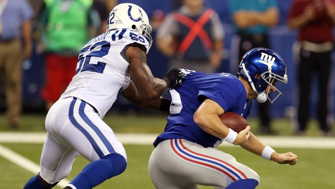 Giants quarterback Eli Manning, right, is sacked by Indianapolis linebacker D'Qwell Jackson in the first half on Saturday night.