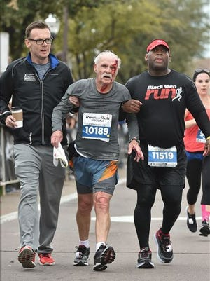 """Flanked by a fellow runner and a spectator, John Wilkie continues toward the half-marathon finish line. """"These two guys just fell out the sky like angels and picked me up,"""" he says."""