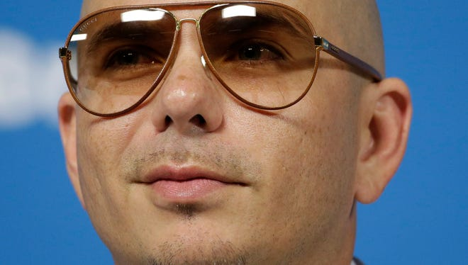In this Wednesday, June 11, 2014, file photo, Cuban-American rapper Pitbull listens to a question during a news conference one day before the World Cup soccer tournament starts in Sao Paulo. (AP Photo/Felipe Dana, File)