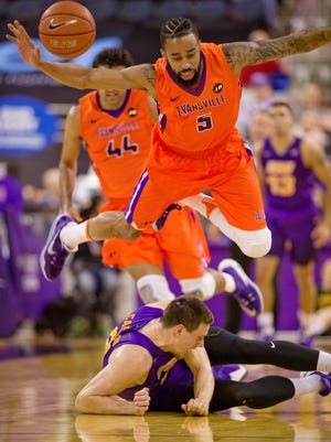 Evansville's Solomon Hainna launches himself over Northern Iowa's Klint Carlson while going for a loose ball in the first half of their game at The Ford Center in Evansville Sunday afternoon. The Purple Aces beat the Panthers 70-58.