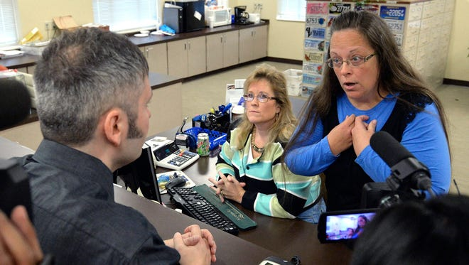 FILE - In this Sept. 1, 2015, file photo, Rowan County Clerk Kim Davis, right, talks with David Moore following her office's refusal to issue marriage licenses at the Rowan County Courthouse in Morehead, Ky. Months after the Supreme Court effectively legalized same-sex marriage, some lawmakers across the U.S. are proposing laws that would give businesses and some public employees the right to refuse service for gay couples based on their religious beliefs. The bills, proposed mostly by Republicans, aren't universally backed in the party and top employers, including Delta Air Lines, Home Depot, Porsche and UPS warn the proposals are unwelcoming and bad for business.