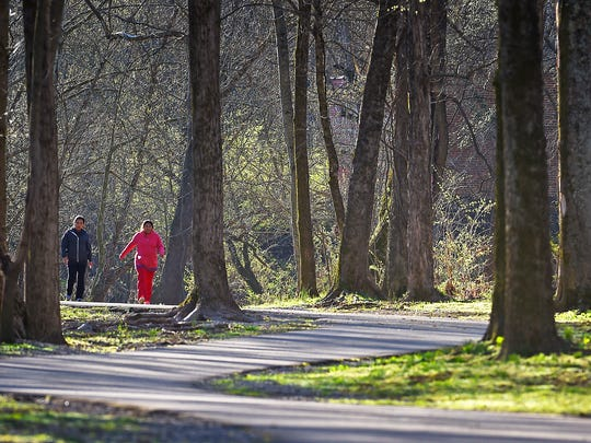 Residents walk the Springfield Greenway on Friday.