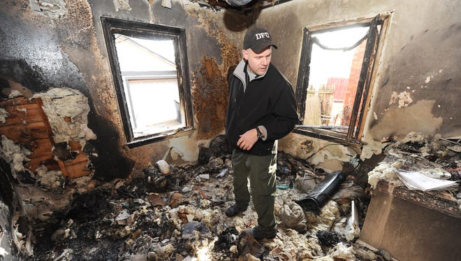 Lt. Joseph Crandall, an arson investigator for the Detroit Fire Department, examines a suspicious fire on Westphalia Street in December.