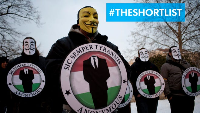 "Protestors wearing Guy Fawkes masks hold the logos of the international hacker group Anonymous during a demonstration against Anti-Counterfeiting Trade Agreement in Budapest, Hungary, in February 2012.  The ""hacktivist"" group announced Nov. 2, 2015, they were going to release data on 1,000 KKK members."