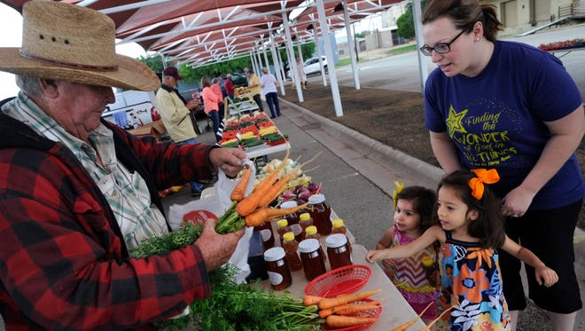 Mack Boyd bags a handful of carrots for Marisa Vazquez and her two daughters; Olivia, 2, and Ella, 3. Marisa and her husband David braved the rain and brought their family to the Abilene Farmer's Market Thursday morning June 1, 2017.
