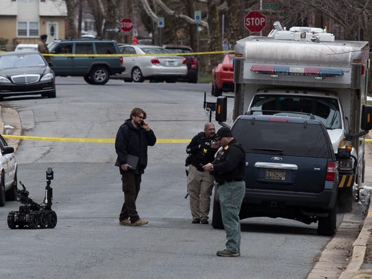 Law enforcement agencies investigate an Elsmere home after a pipe bomb blew up in front of it on March 12.