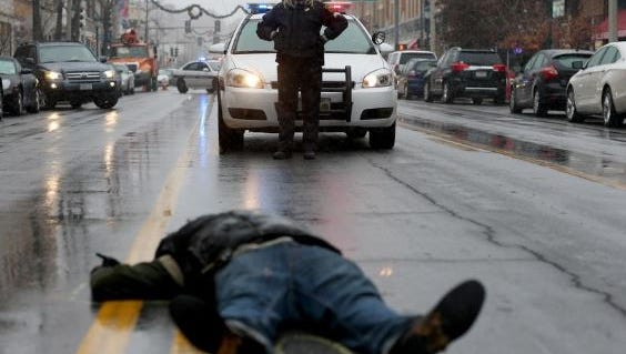 A Washington University in St Louis police officer looks on as a demonstrator lays on the ground during a mock death protest of the shooting death of Michael Brown by a Ferguson police officer on November 16, 2014 in St. Louis, Missouri.