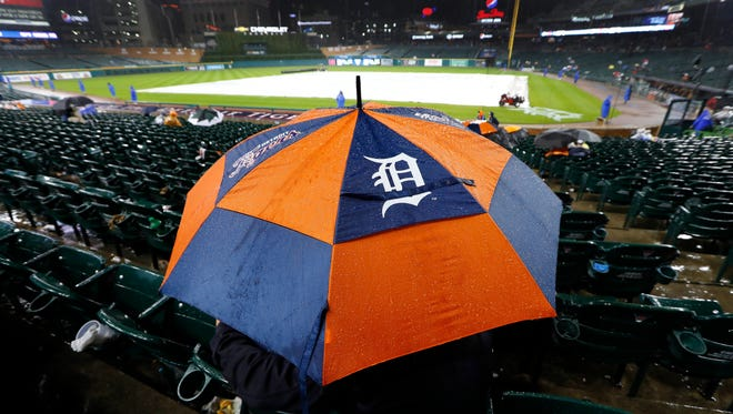 Detroit Tigers fans sit under an umbrella during a rain delay in the third inning of a baseball game between the Detroit Tigers and Cleveland Indians in Detroit, Wednesday, Sept. 28, 2016.