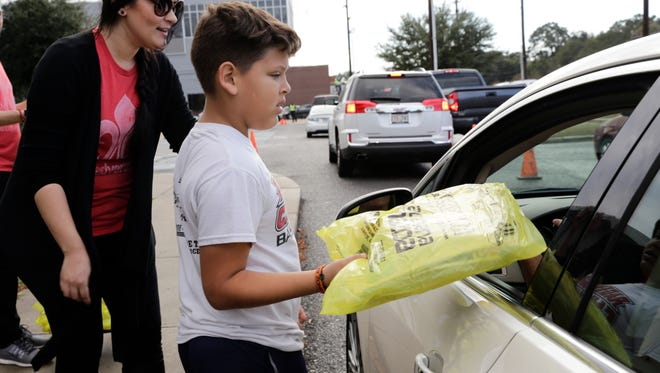 Isaac Perez hands a newspaper to a motorist during the Daily Advertiser's pre-sale of the Thanksgiving day edition which feature Black Friday advertisements, in Lafayette Nov. 23, 2016.