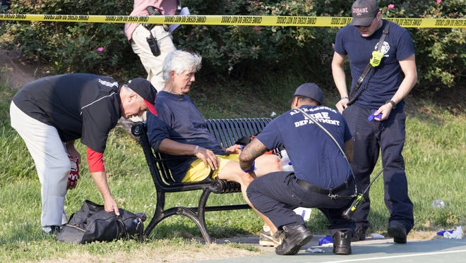A man receives medical attention from first responders on the scene following a shooting in Alexandria, Va.  A gunman opened fire on a Republican congressional team practice Wednesday and at least one congressman was wounded, authorities said. Multiple congressman at the scene said Rep. Steve Scalise, R-La., was among those wounded. Police said a suspect was believed to be in custody.