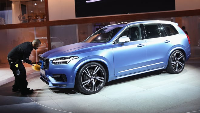 A worker prepares the new Volvo XC90  to be introduced at the North American International Auto Show in Detroit last January