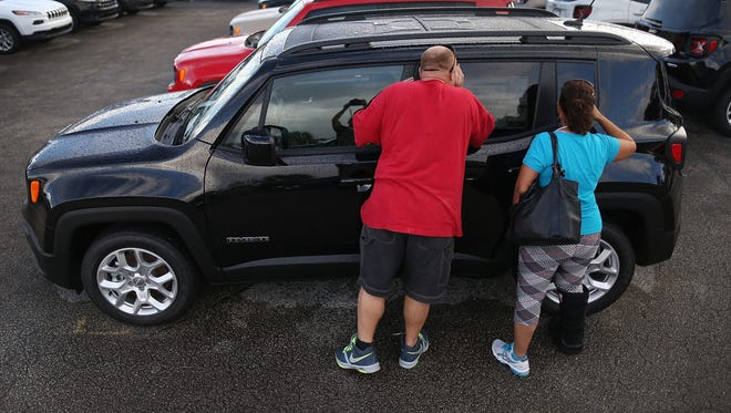 Marquez Giovanny and Susy Menostao check out a Jeep Renegade for sale at the Hollywood Chrysler Jeep dealership  in Hollywood, Fla.
