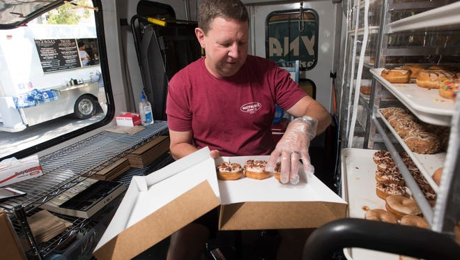 Danny DeWitt, the owner of Maynard's Donut, Co., fills a customers order from his company's new food truck parked outside city hall in downtown Pensacola, Tuesday, April 10, 2018.