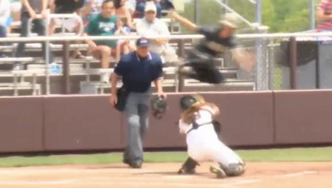 Kasey McCravey hurdles the catcher to avoid the tag and score the run.