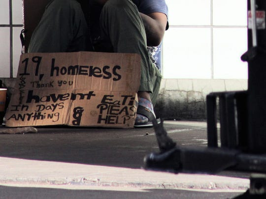A homeless teenager sits on sidewalk with cardboard sign begging for food and help.