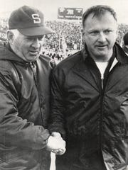 Michigan coach Bo Schembechler, right little to smile about as he greets Michigan State coach Duffy Daugherty in middle of the playing field after the Michigan—Michigan State game in East Lansing in 1969. Daugherty's Spartans defeated Bo's Wolverines 23-12 before a sellout crowd.