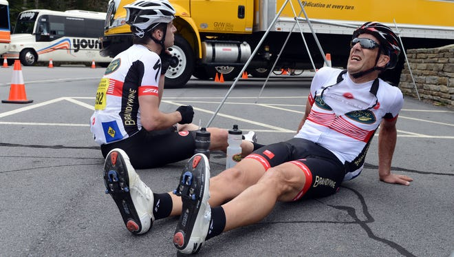 From left, cyclists Matt Neugebauer and Jae Walker recover at the summit of Mount Mitchell after a five-hour ride in the Assault.