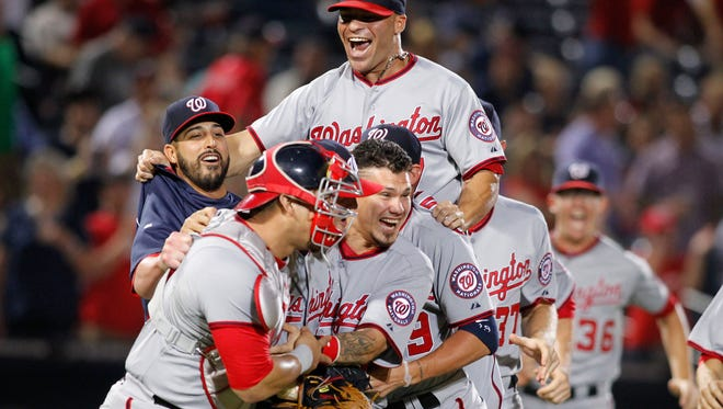Washington Nationals catcher Wilson Ramos (40) and relief pitcher Drew Storen (22) and catcher Jose Lobaton (59) and left fielder Scott Hairston (7) celebrate a victory against the Atlanta Braves at Turner Field. The Nationals defeated the Braves 3-0 to clinch the National League eastern division championship.